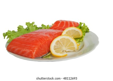 Salted salmon with lemon on salad leaves isolated over white background