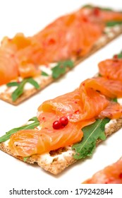 Salted salmon on crispy bread with cheese and arugula, closeup
