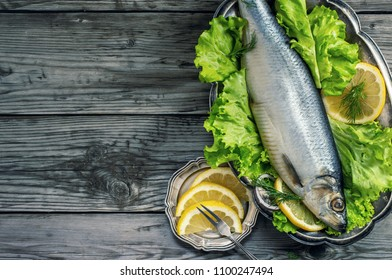 Salted whole herring with leaf lettuce on rustic wooden background, top view with copy space