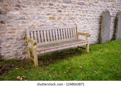Saltford, UK, 11-25-2018: Wooden Seat in the Graveyard of St Marys Church, Saltford, Just outside the town of Bath