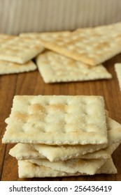 Saltine Crackers on a wooden table top or counter.