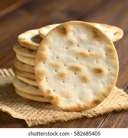 Saltine or soda crackers, photographed on dark wood with natural light (Selective Focus, Focus on the standing cracker)