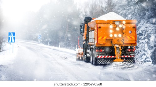 Salting highway maintenance. Snow plow truck on snowy road in action. Hard weather condition in winter. Gritter vehicle spreading deicing salt.