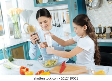 Salting. Pretty happy dark-haired mother and daughter smiling and salting and peppering salad while cooking