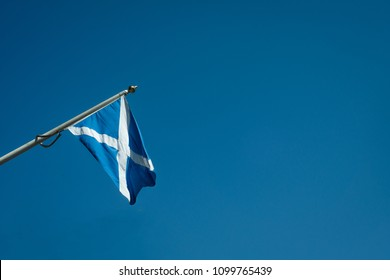 Saltire Flag Flying in a Sunny Blue Sky in Edinburgh, Scotland