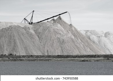 The salt-mine in the form of a hill with conveyor rocks. The foreground is an artificial pond. Black and white image