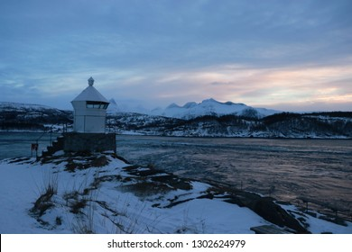 SALTSTRAUMEN, NORDLAND COUNTY / NORWAY - JANUARY 26 2019: Saltstraumen lighthouse in Norway with mountaintops with snow in the background