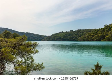 The saltwater blue bright turquoise colored lakes of at the National Park on the island Mljet, Croatia. Mediterranean adriatic coast with a blue sky and greenery creating a calm mindful serene scene