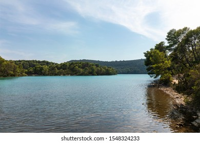 The saltwater blue colored lakes of malo and veliko jezero at the National Park on the island Mljet, Croatia. Mediterranean adriatic coast with a blue sky and greenery creating a calm serene scenery