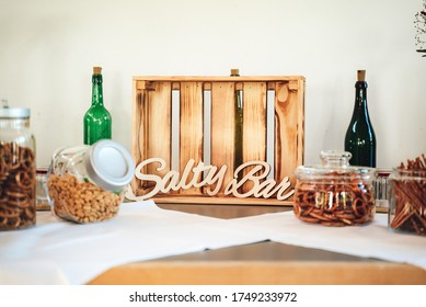 """Salty bar of several kinds snacks decorated on wooden table. Closeup of lettering: """"Salty Bar"""". Wedding or party concept."""