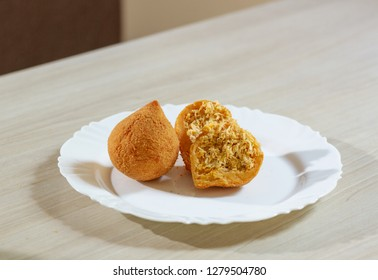 "Salty ""coxinha"" in white dish cut and whole. Traditional Basle snack"