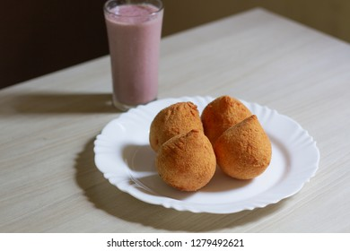 "Salty ""coxinha"" in white plate and glass of juice to the side. Traditional Basle snack."