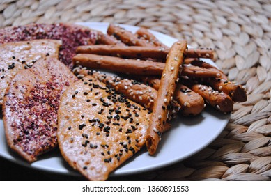 salty crackers close up on hay background and gray plate sesame sumac biscuits.