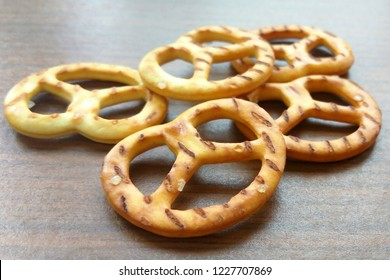 Salty crispy cracker mini pretzels on wooden table background. Close up photography.