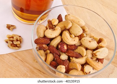 Salty and crunchy mixed nuts with a tall glass of lager beer