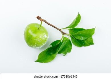 Salty green plum with green leaves flat lay on a white background