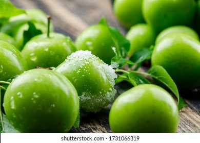 Salty green plums with leaves on wooden background, close-up.