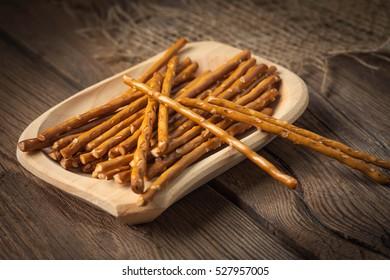 Salty pretzel sticks on a dark wooden table.