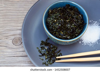 Salty roasted dried seaweed nori with sesame seeds in a blue bowl on old wooden table.Healthy snack,Korean food concept.