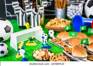 Salty snacks and beer on the table for soccer party.