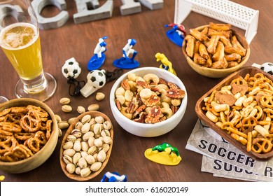 Salty snacks and drinks on the table for soccer party.