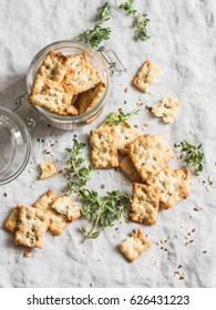 Salty sunflower seeds and thyme crackers on a light table, top view. Delicious snack
