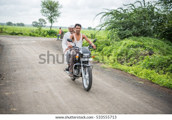 SALUNKWADI, INDIA - August 12, 2016: Rural people daily lifestyle, Indian rural man riding motorbike in rural village Salunkwadi, Ambajogai, Beed, Maharashtra, India, Southeast Asia.