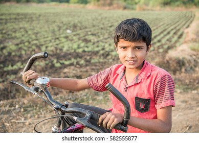 SALUNKWADI, INDIA â?? November 13, 2016: Indian boy playing bicycle in farm in rural village Salunkwadi, Ambajogai, Beed, Maharashtra, India, South East Asia.