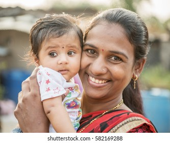 SALUNKWADI, INDIA - November 14, 2016: Indian Hindu mother playing with new born baby, people daily lifestyle in rural village Salunkwadi, Ambajogai, Maharashtra, India, Southeast, Asia