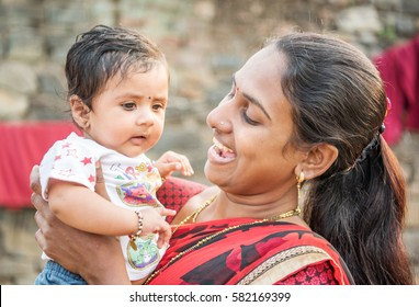 SALUNKWADI, INDIA - November 14, 2016: Indian Hindu mother playing with new born baby, people daily lifestyle in rural village Salunkwadi, Ambajogai, Maharashtra, India, Southeast, Asia