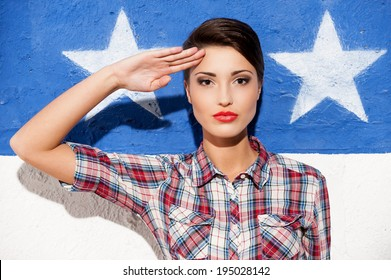 Salute! Fashionable young short hair woman in casual shirt posing against American flag background