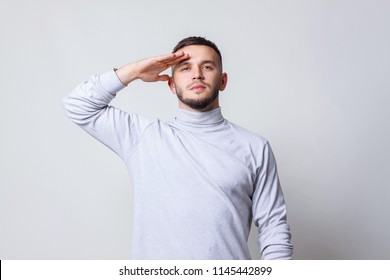 Saluting concept. Young man in casual white turtleneck shirt saluting with hand at forehead on a gray background copy space