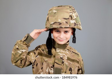 Saluting soldier. Young boy dressed like a soldier isolated on gray background