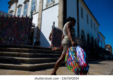 Salvador, BA, Brazil. April 12, 2019. Baiana passes selling tapes of Our Lord of Bomfim in front of the church of the same name. One of the main tourist sights of the state.