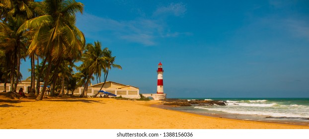 SALVADOR, BAHIA, BRAZIL: Farol De Itapua on the rough sea. Tropical landscape on the beach with palm trees and lighthouse