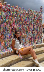 Salvador, Brazil - 5 February 2019: woman posing in front of wish ribbons at Bonfim church in Salvador Bahia on Brazil
