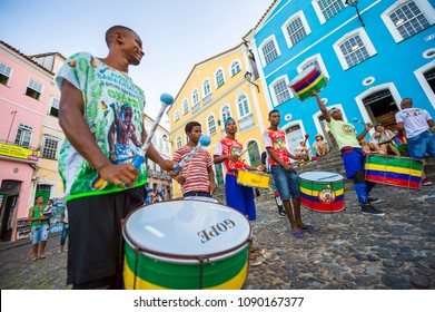 SALVADOR, BRAZIL - CIRCA FEBRUARY, 2018: Group of energetic young men play drums in front of colorful colonial buildings in the historic Pelourinho neighborhood.