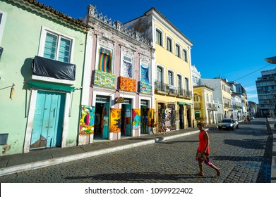 SALVADOR, BRAZIL - CIRCA FEBRUARY, 2018: Pedestrians and cyclist pass in front of colorful colonial buildings displaying and selling bright souvenir sarongs in the historic Pelourinho neighborhood.