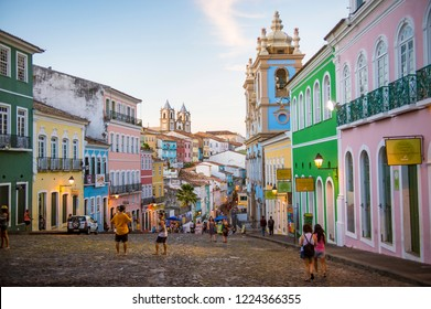 SALVADOR, BRAZIL - CIRCA MARCH, 2018: Tourists take pictures of the colorful colonial architecture lining the cobblestone hills of Pelourinho.