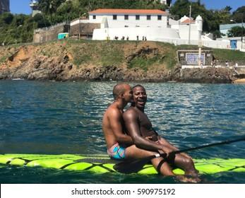 SALVADOR, BRAZIL - FEB 26, 2017: Black gay couple on a Stand Up Board Paddling , Porto da Barra Beach.