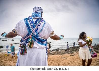 SALVADOR, BRAZIL - FEBRUARY 02, 2016: A Brazilian candomble priest performs a blessing at the Festival of Yemanja in traditional blue and white robes with colorful beads on the beach at Rio Vermelho.