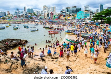 SALVADOR, BRAZIL - FEBRUARY 02, 2016: Celebrants at the Festival of Yemanja in Rio Vermelho take traditional Brazilian fishing boats to leave religious offerings at sea for Goddess of the Waters.