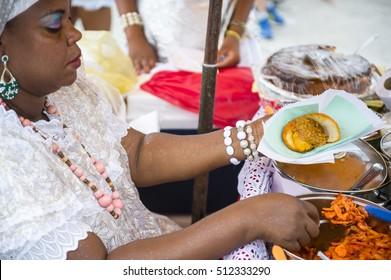 SALVADOR, BRAZIL - FEBRUARY 02, 2016: Brazilian woman assembles a plate of traditional acaraje fritters from a stall on the street.