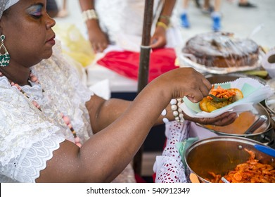 SALVADOR, BRAZIL - FEBRUARY 02, 2016: Brazilian Baiana woman assembles a plate of traditional acaraje fritters from a stall on the street.