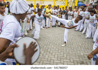 SALVADOR, BRAZIL - FEBRUARY 02, 2016: Brazilian capoeira group performs for a crowd at an outdoor festival in the Rio Vermelho neighborhood. Slow shutter speed motion blur.
