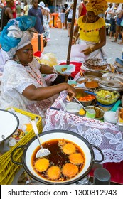 SALVADOR, BRAZIL - FEBRUARY 2, 2016: Women in traditional Baiana dresses fry Brazilian acaraje fritters in the thick brown oil of the dende palm fruit at a street food stall at the Yemanja Festival.