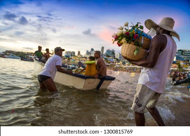 SALVADOR, BRAZIL - FEBRUARY 2, 2016: Celebrants at the Festival of Yemanja carry flowers to a boat on Rio Vermelho beach to leave as an offering at sea for the Goddess of the Waters.