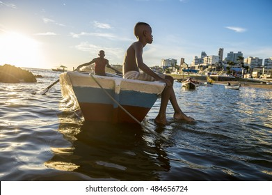 SALVADOR, BRAZIL - FEBRUARY 20, 2016: Brazilians wait for celebrants at the Festival of Yemanja to take traditional boat at the fishing village of Rio Vermelho to leave religious offerings at sea.