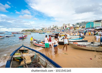 SALVADOR, BRAZIL - FEBRUARY, 2016: Fishermen at the village of Rio Vermelho provide their small fishing boats to celebrants at the Festival of Yemanja to take to sea to leave religious offerings.