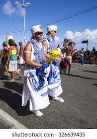 SALVADOR, BRAZIL - FEBRUARY 5, 2013: Members of the Filhos de Gandhi religious group walk in traditional blue and white costume during a carnival street party.